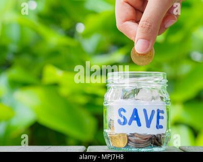 Abstrakte Geld sparen Hand halten und Münze zu Glas Glas Münzen auf Holz Tisch mit grünen Bäumen Hintergrund - Stockfoto