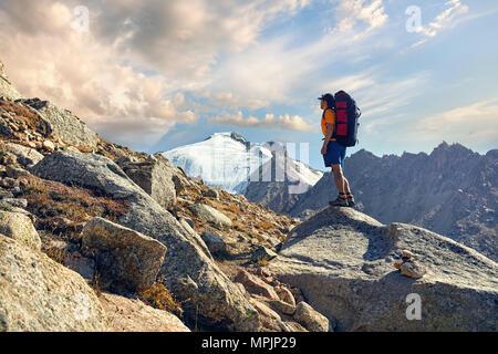 Wanderer in orangefarbenen T-Shirt mit großem Rucksack auf der Suche auf dem verschneiten Gipfel im Hintergrund - Stockfoto
