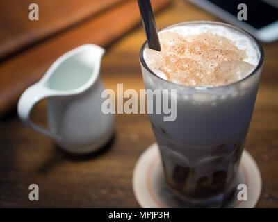 Eis Kaffee mit Milch Sahne in hohes Glas mit dunklen braunen Stroh innen und Handy, Leder Buch auf hölzernen Tisch Vintage Style - Stockfoto