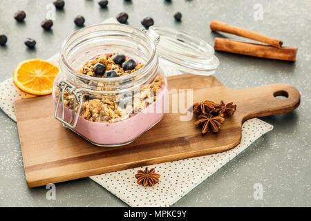 Rosa, Obst, Joghurt mit Müsli und Blaubeeren in einem Glas auf einem hölzernen Schneidebrett und Zimt Gewürz auf einem grauen Küche Zähler - Stockfoto