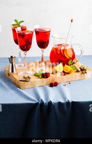 Frische Sommer rote Sangria aus reifen Früchten und Beeren sowie Wein auf dem Tisch in Gläsern und einer Karaffe. Gewürzen und Minze - Stockfoto