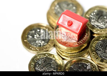 Makro Nahaufnahme eines kleinen Hauses ruht auf neue Pfund Münzen mit einem weißen Hintergrund. - Stockfoto