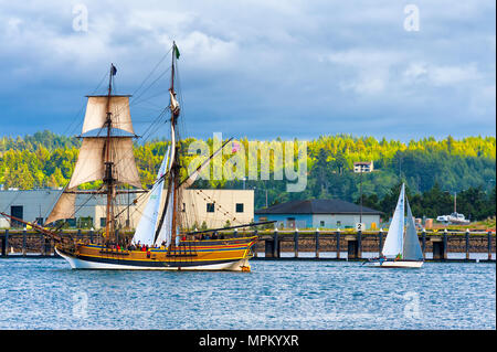 Newport, Oregon, USA - 25. Mai 2016: Tall Ship Lady Washington fährt in Yaquina Bay und durch andere kleinere Schiffe in Newport Oregon verbunden - Stockfoto