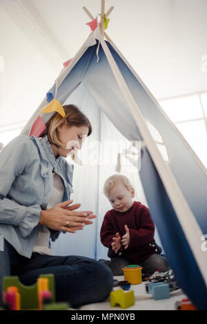 Mutter spielt mit ihrem Sohn in einem Zelt zu Hause - Stockfoto