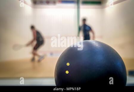 Double Dot squash Ball mit zwei Spielern im Hintergrund - Stockfoto