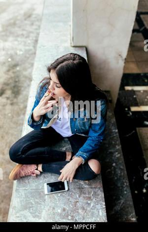 Junge Frau sitzt auf einer Wand das Rauchen einer Zigarette - Stockfoto
