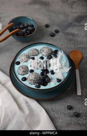 Blau smoothie Schüssel mit Kokosraspeln, Blaubeeren und Drachenfrucht Kugeln - Stockfoto