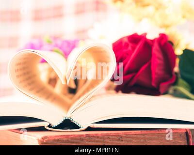 Retro geöffnete Buch und Seiten die Herzform mit Blume im backgroung. Liebe und Valentinstag Konzept. - Stockfoto