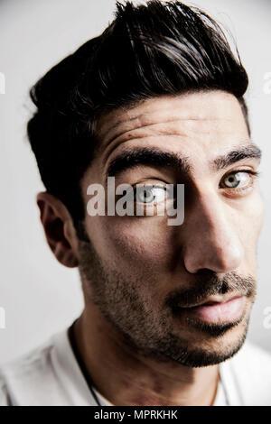 Portrait von skeptischen jungen Mann, seine Augenbraue - Stockfoto