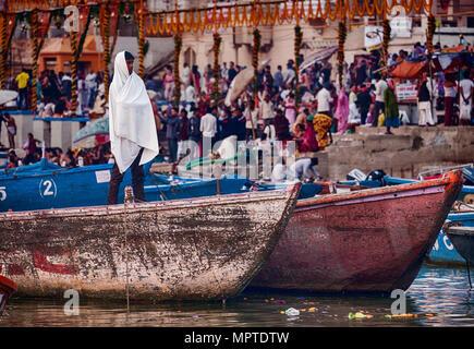 VARANASI, INDIEN - 15. NOVEMBER 2016: Am Morgen nach dem Dev Diwali festical, ein anonymer junger Mann ist verpackt in einer auf einem Boot, ausgeblendet. - Stockfoto
