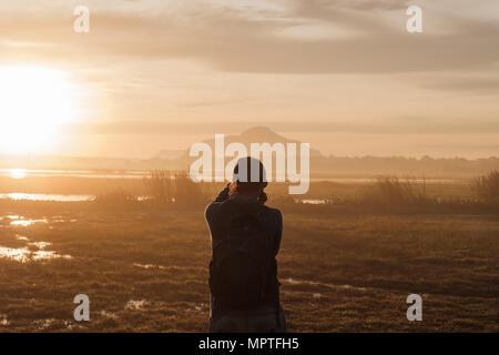 Silhouette einer Frau mit einem Smartphone Bilder aufnehmen bei Sonnenaufgang oder Sonnenuntergang. - Stockfoto