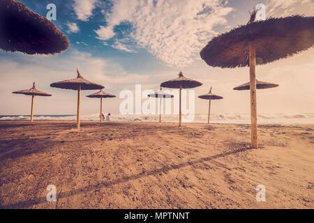 2 Frauen am Strand mit viel Stroh Sonnenschirme bewundern, das Meer und die Wellen an einem schönen Sommertag - Stockfoto