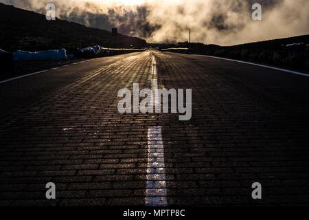 Asphalt und weiße Linien in die Hölle gehen, dramatische Szene für Angst und Schrecken Konzept, Wolken mit Sonnenlicht hinter den langen Richtung und. - Stockfoto