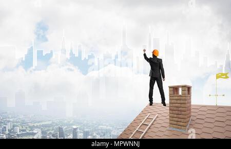 Mann Architekten zeichnen Silhouette der modernen Stadt am blauen Himmel. Mixed-media - Stockfoto