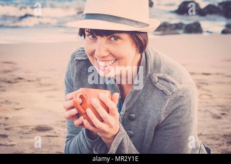 Nett lächelnden jungen Frau sitzen unten am Strand mit Blick auf das Meer im Hintergrund. trinken eine Tasse Tee oder Kaffee für eine Freizeitaktivität relalxed und angeschlossen - Stockfoto
