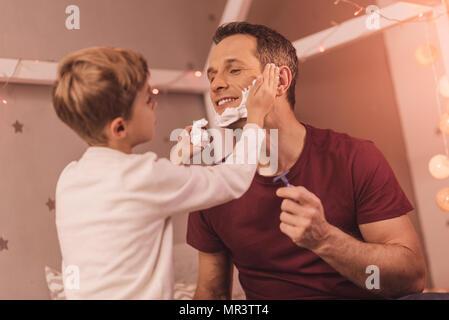 Sehr netter Junge hilft seinem Vater zu rasieren - Stockfoto