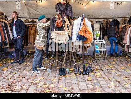 Berlin Prenzlauer Berg. Mauerpark Flohmarkt. Junge trendige Shopper an Second Hand Kleidung stall verkaufen Mäntel, Taschen und Schuhe - Stockfoto
