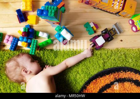 Kleine Junge auf dem Teppich mit Spielzeug im Spielzimmer - Stockfoto