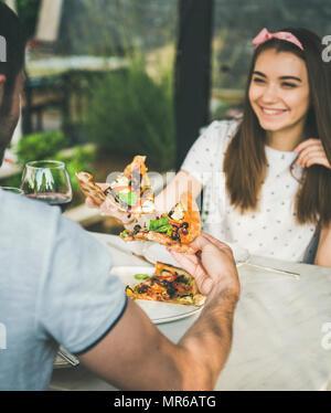 Junge glücklich kaukasischen Paar am Tisch essen Pizza und trinken Wein in der Italienischen Küche Cafe an sonnigen Sommertagen sitzen - Stockfoto