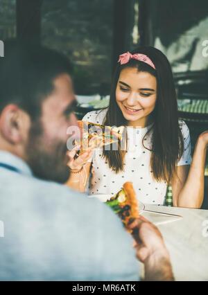 Junge glücklich kaukasischen Paar am Tisch essen Pizza in der Italienischen Küche Cafe an sonnigen Sommertagen sitzen - Stockfoto