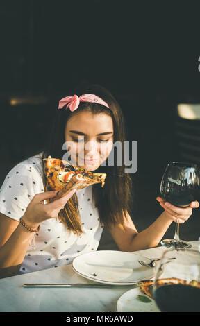 Junge glücklich kaukasische Frau am Tisch essen Pizza und trinken Rotwein in Outdoor italienische Küche Cafe auf klaren sonnigen Sommertag sitzen, Platz kopieren - Stockfoto