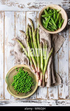 Vielzahl von Roh ungekocht organische Junge grüne Gemüse, Spargel, Erbsen, pod Erbse in keramischen Platten auf Leinen über weiß Holzbrett Hintergrund. T