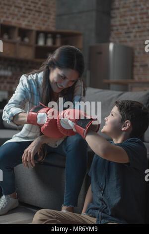 Little Boy und seine junge Mutter fistbumping beim Tragen Boxhandschuhe - Stockfoto