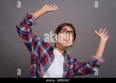 Junge schöne Kasachische Frau gegen grauer Hintergrund - Stockfoto