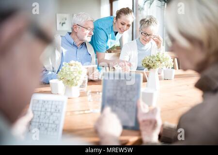 Ältere Erwachsene Spiele spielen auf digitale Tabletten in der Pflege zu Hause. - Stockfoto