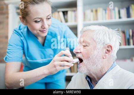 Care worker helfen älteren Mann mit Inhalator. - Stockfoto