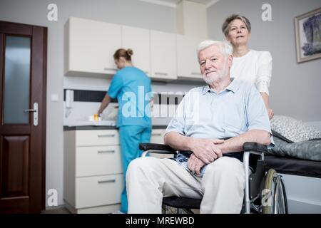 Älterer Mann im Rollstuhl mit Frau in der Pflege zu Hause. - Stockfoto