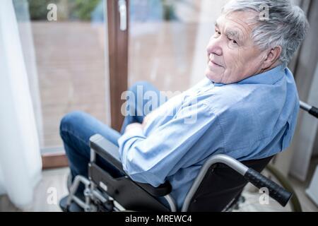 Älterer Mann im Rollstuhl durch die Fenster in der Pflege zu Hause. - Stockfoto