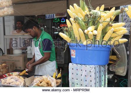 Eine Indische gilt Chili Pulver und andere Gewürze zu gegrilltem Mais-auf-die-Cob in Little India in Toronto, Ontario, Kanada. - Stockfoto
