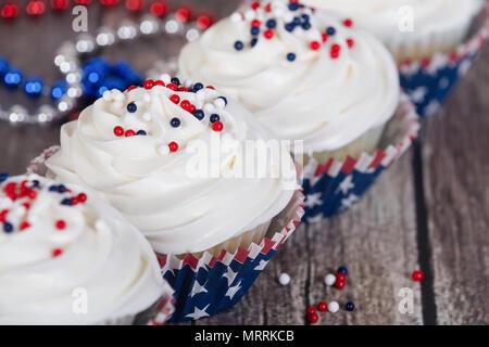 Patriotische 4. Juli oder Memorial Day Feier Cupcakes auf rustikalen Holztisch mit festlichen roten, weißen und blauen Verzierungen. - Stockfoto