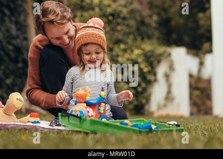 Vater und Tochter sitzt im Park und mit Spielzeug spielen. Vater und Tochter verbringen die Zeit zusammen an einem Park. - Stockfoto