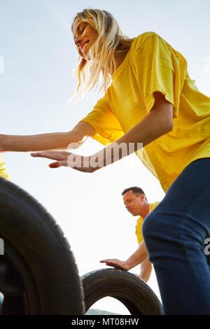 Junge Frau rollt ein Autoreifen in einen Wettbewerb, der sich an ein Teambuilding Event - Stockfoto