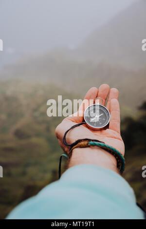 Gestärkter Palm mit Kompass. Blick auf den Kompass, um zu herauszufinden, richtige Richtung. Nebligen Tal und die Berge im Hintergrund. Santo Antao. Kap Cabo Verde - Stockfoto