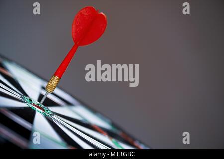 Nahaufnahme rot Dart Pfeile im Target Center auf dunklem Hintergrund. Business Target oder Erfolg Ziel und Sieger Konzept. - Stockfoto