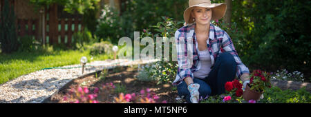 Schöne weibliche Gärtner an Kamera suchen und lächelnd Holzkiste voller Blumen in Ihrem Garten gepflanzt werden. Gartenarbeit Konzept. - Stockfoto