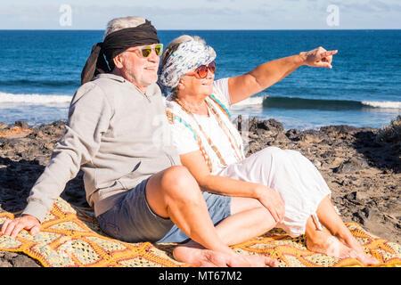 Paar glücklich Senior im Alter von kaukasischen Völker sitzen am Ufer am Strand genießen Sie den Sommer und die Sonne. Hippies alternative Kleidung für - Stockfoto