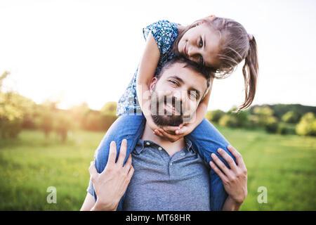 Vater einer kleinen Tochter piggyback Ride im Frühjahr die Natur. - Stockfoto