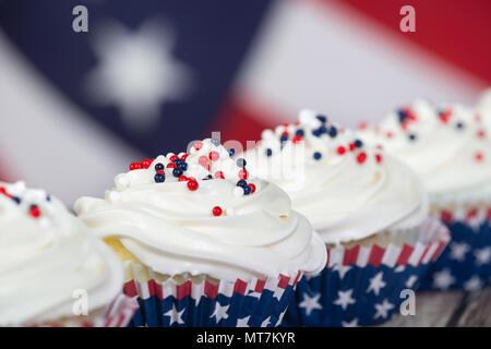 Patriotische 4. Juli oder Memorial Day Feier Cupcakes, close-up. Die amerikanische Flagge im Hintergrund. - Stockfoto