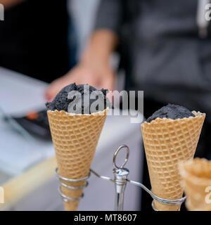 Zwei Waffeln, Hörner mit Kugeln von trendiges schwarzes Eis und Hand des Verkäufers. Köstliche Kühlung Teil zum Spaß. Selektive konzentrieren. Reale Szene speichern. - Stockfoto