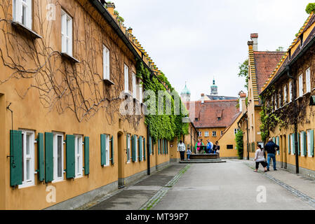 AUGSBURG, DEUTSCHLAND - 20. MAI 2018: Besucher in der Nähe von Gut in der Fuggerei in Augsburg Stadt. Augsburg ist eine Stadt in Schwaben, Bayern, es ist die drittälteste c - Stockfoto