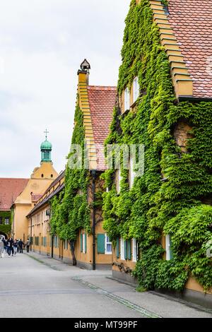 AUGSBURG, DEUTSCHLAND - 20. MAI 2018: Besucher in der Nähe der St. Mark's Church in der Herrengasse Straße in der Fuggerei in Augsburg Stadt. Augsburg ist eine Stadt in Swa - Stockfoto