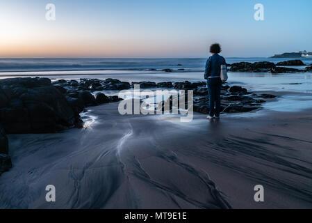 Malerischer Blick auf Frau suchen auf See gegen Himmel während des Sonnenuntergangs. - Stockfoto