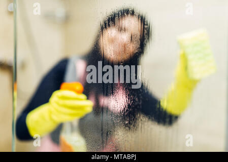 Zimmermädchen in Handschuhe Glas reinigt mit einem Reinigungsspray, hotel Bad für den Hintergrund. Professionelle allgemeine Ordnung und Sauberkeit, die Putzfrau - Stockfoto