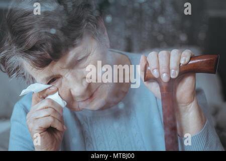 Traurig senior Weinen, holding Stock und Gewebe
