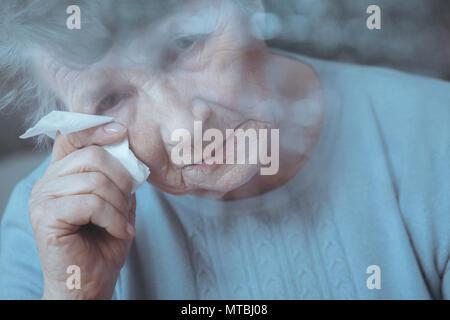 Portrait von traurig, einsam ältere Frau weinen, holding Gewebe