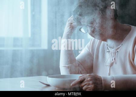 Ältere Frau Ablehnung essen, sitzen neben Tabelle